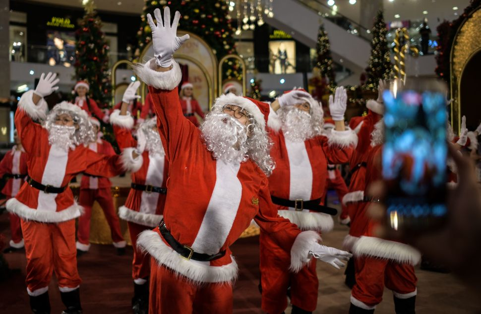 Performers clad in Santa Claus outfits dance at a shopping mall in Kuala Lumpur, Malaysia, on Dec. 18, 2017.