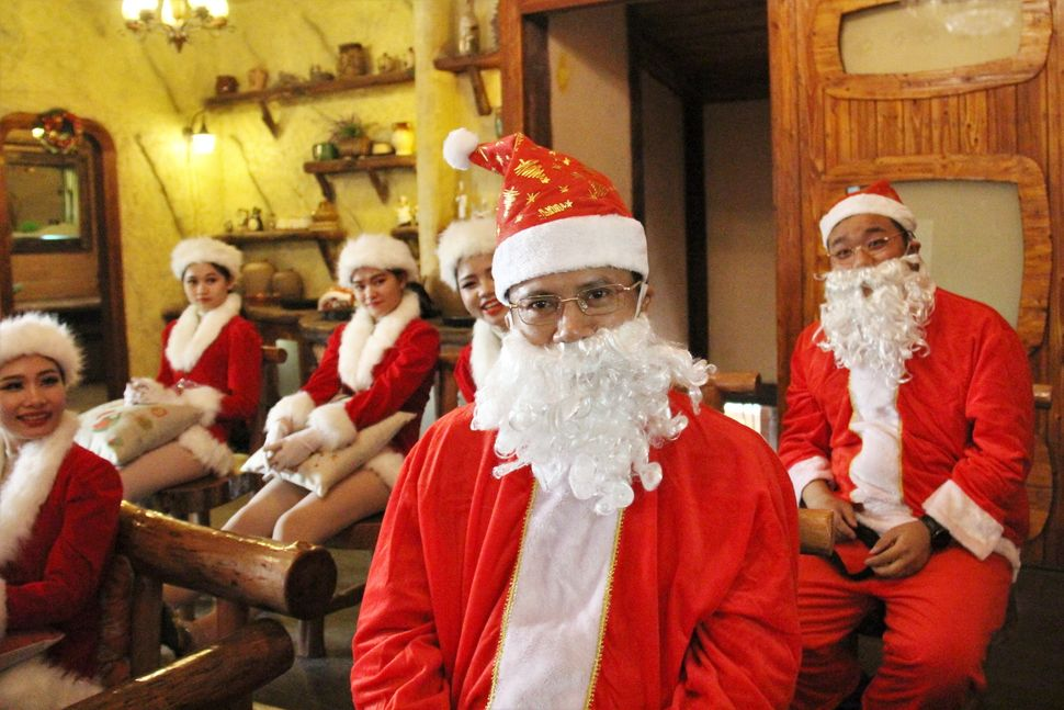 Trainees in Santa Claus outfits practice being Santa during a training course at Chuanlord Tourism & Leisure Expo Park on