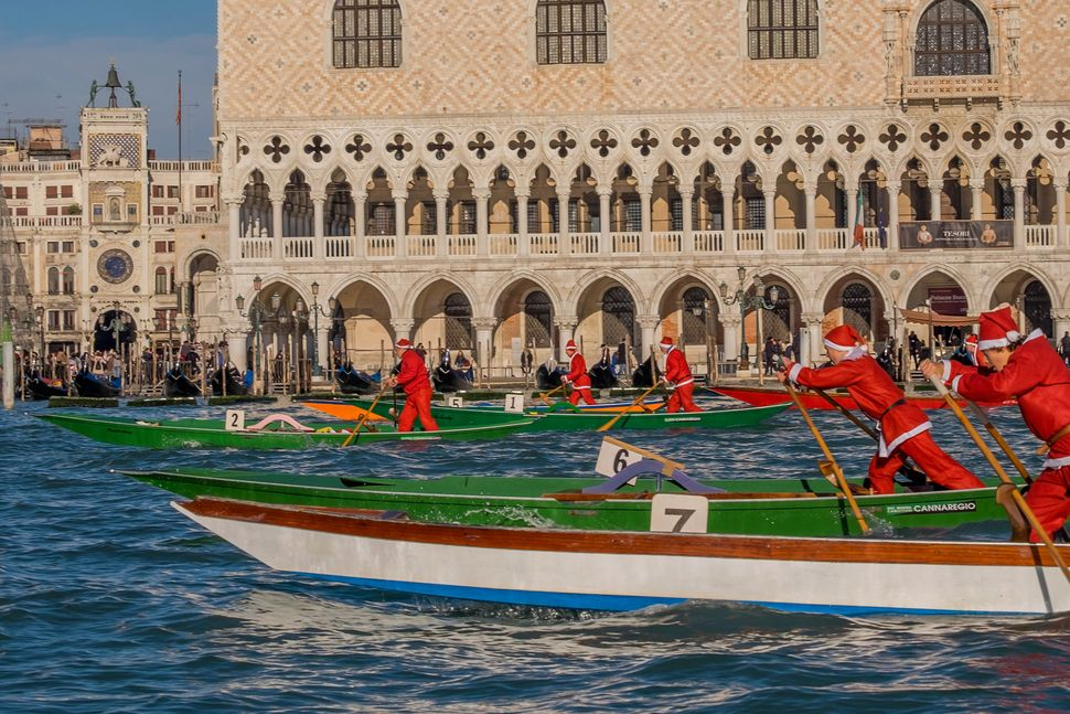 Rowers dressed as Santa take part in the annual Father Christmas Regatta organized by University Ca' Foscari on the Grand Can