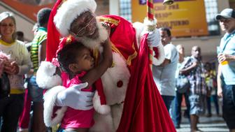 TOPSHOT - Hilton dos Santos, 84, is hugged by a little girl in the Central Station of Rio de Janeiro, Brazil, on December 15, 2017.  He has been dressing up as Santa Claus for the past five years, after attending a Santa Claus School. / AFP PHOTO / MAURO PIMENTEL        (Photo credit should read MAURO PIMENTEL/AFP/Getty Images)
