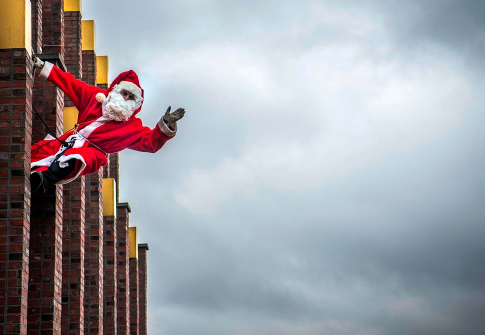 A man dressed as Father Christmas aka Santa Claus poses on the top of the Kollhoff tower in front of a Berlin skyline, on Dec
