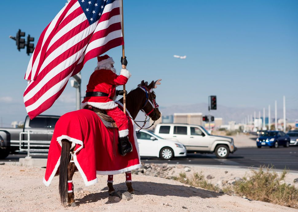 Rafael Evelio Sarabia, dressed as Santa Claus on horseback, waves to passing traffic along Las Vegas Bouelvard in Las Ve