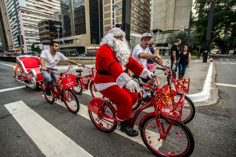 A Santa Claus rides a bike on Avenida Paulista, just a week ahead of Christmas in Sao Paulo, Brazil.
