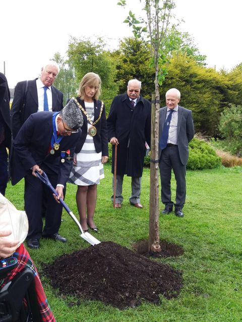 Councillor Dr. James Shera, a leading Pakistani Christian, plants a friendship tree while wearing a Pakistani Jinnah cap in t