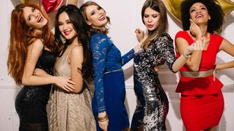 Group of beautiful young girls having night out . Standing in front of a white wall, laughing and dancing . Wear elegant dresses. Room is decorated with star and heart  shaped balloons.