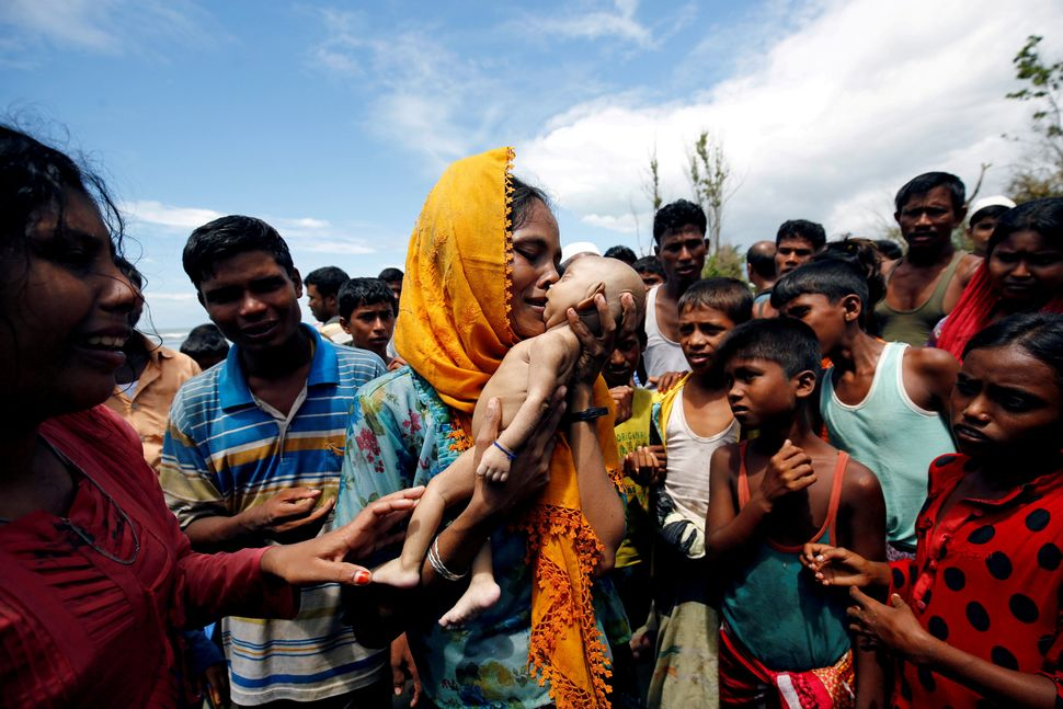 Hamida, a Rohingya refugee woman, cries as she holds her 40-day-old son, who died as a boat capsized on the shore of Sha