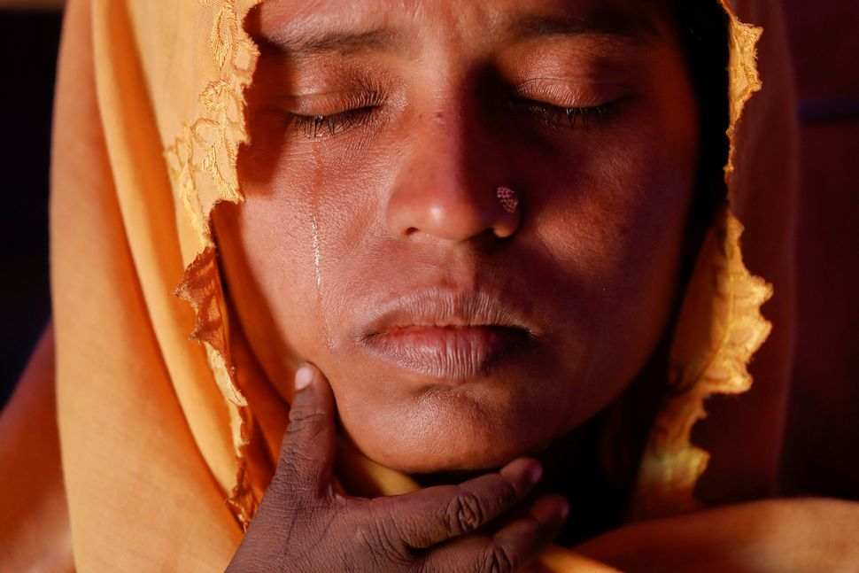 Roshid Jan, a Rohingya refugee who said she is not sure of her age, cries holding her son Muhammad Gyab at their shelter at t