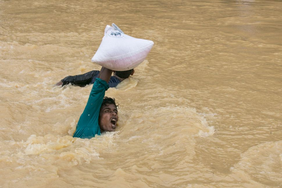 A man struggles to carry supplies across a stream as the monsoon rains continue to make life miserable for the displaced Rohi
