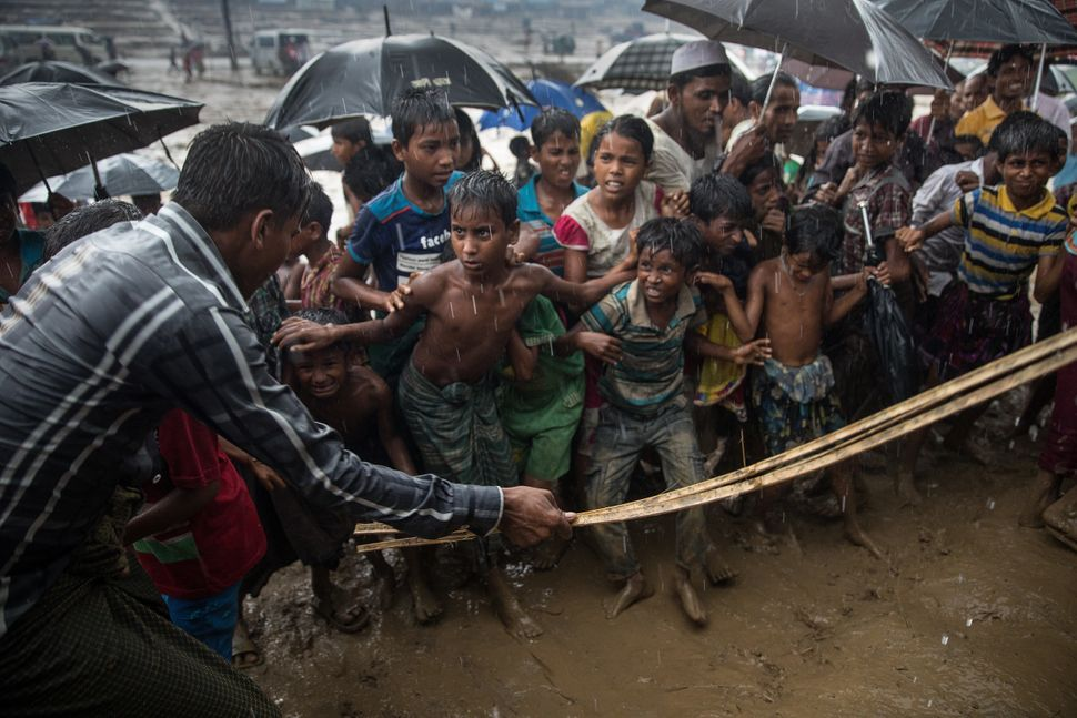 A man hits anxious Rohingya children with a cane as things get out of control during a humanitarian aid distribution on Oct.