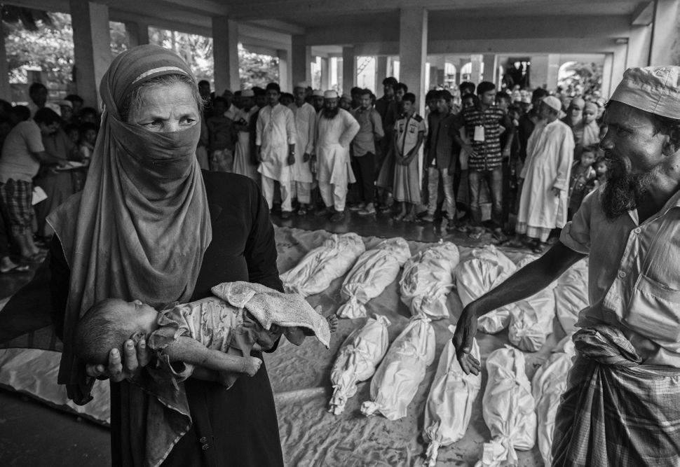 A woman carries the body of a Rohingya refugee baby. Others are seen wrapped in white sheets prior to burial after they died