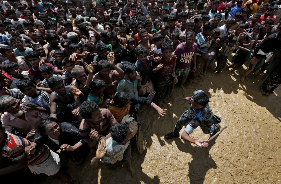 A security officer attempts to control Rohingya refugees waiting to receive aid in Cox's Bazar, Bangladesh, on Sept. 21. Reut