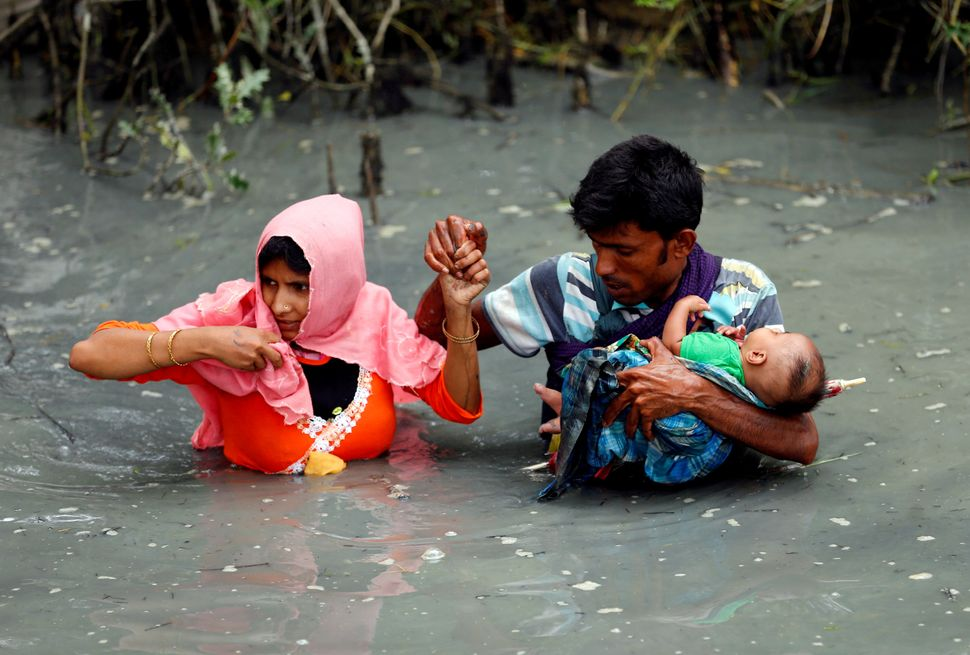 Rohingya refugees carry their child as they walk through water after crossing the border by boat through the Naf River in Tek