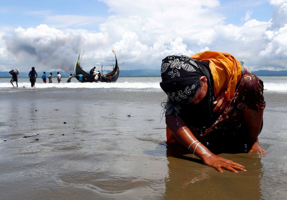 An exhausted Rohingya refugee woman touches the shore after crossing the Bangladesh-Myanmar border by boat through the Bay of
