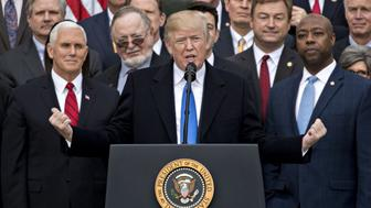 U.S. President Donald Trump, center, speaks during a tax bill passage event with Republican congressional members of the House and Senate on the South Lawn of the White House in Washington, D.C., U.S., on Wednesday, Dec. 20, 2017. House Republicans passed the most extensive rewrite of the U.S. tax code in more than 30 years, hours after the Senate passed the legislation, handing Trump his first major legislative victory. Photographer: Andrew Harrer/Bloomberg via Getty Images