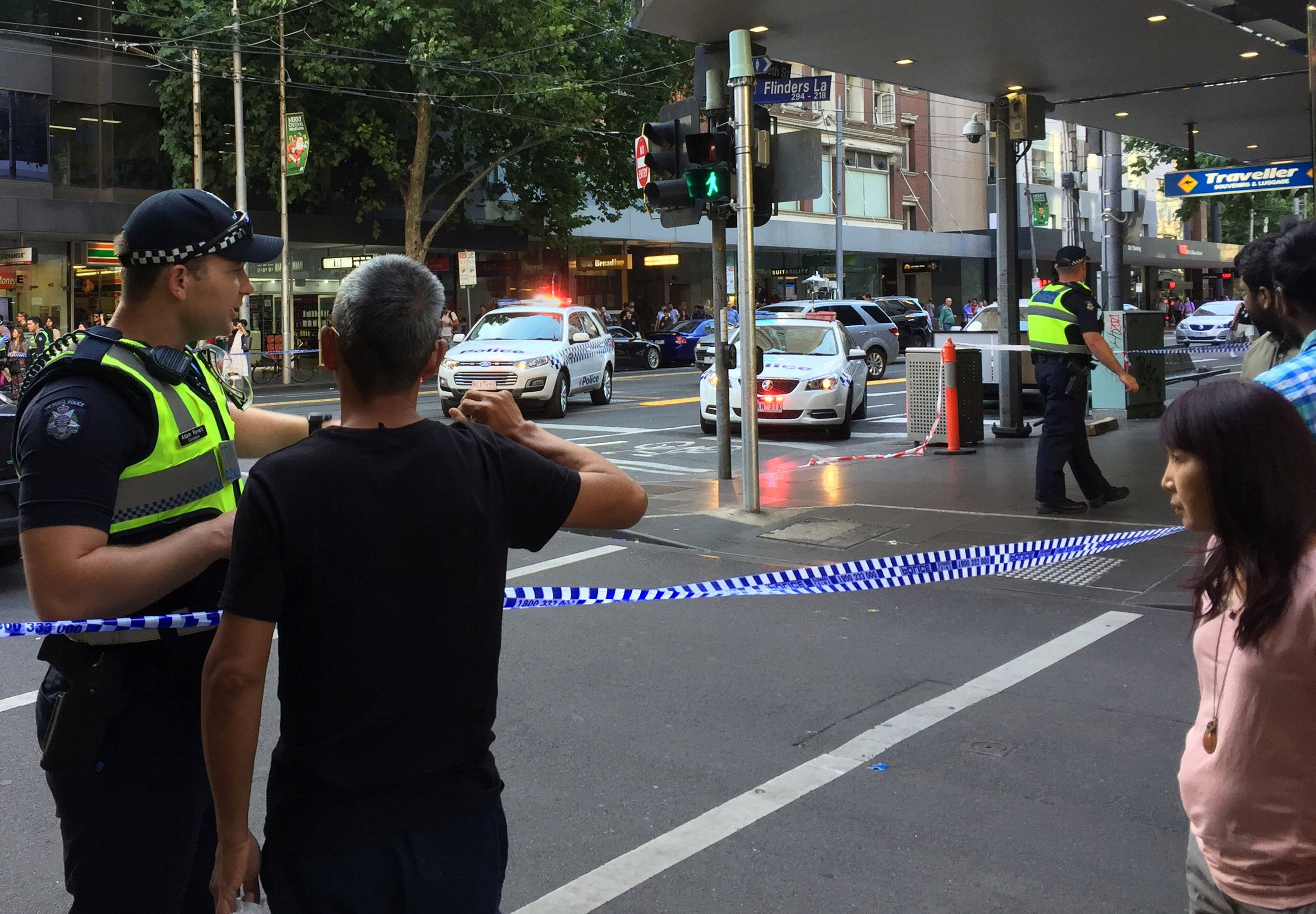 Police officers stand guard as members of the public stand behind police tape after the arrest of the driver of a vehicle that ploughed into pedestrians at a crowded intersection near the Flinders Street train station in central Melbourne, Australia December 21, 2017. REUTERS/Sonali Paul