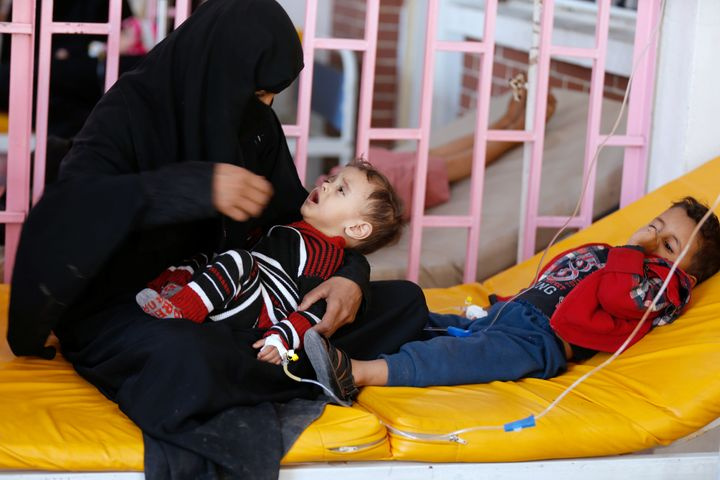 A woman sits with her sons while they are treated at a cholera treatment center in Sanaa, Yemen.
