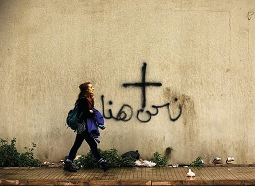 "<em>A woman walks past graffiti depicting a cross and the words ""we are here"" in a Christian-dominated eastern suburb of Beir"