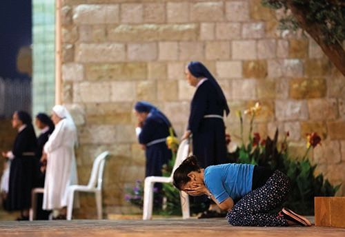 <em>A woman prays alongside Maronite nuns at the Monastery of the Cross in Jal El-Dib north of Beirut (courtesy AFP)</em>