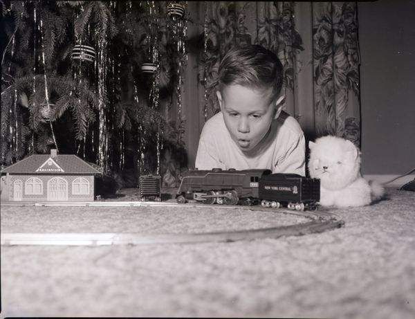 A young boy looks on in wonder as his model train moves around the track in this undated photograph.