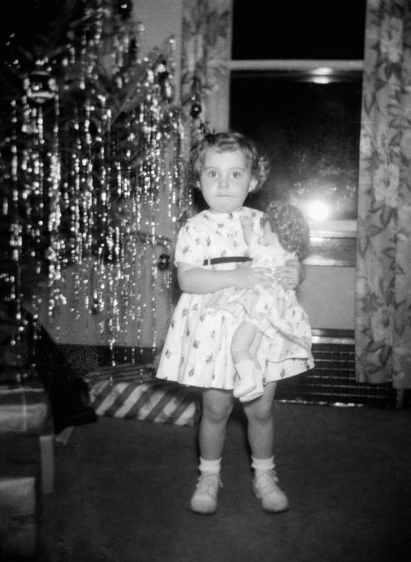 A little girl stands by s Christmas tree clutching her doll in the 1950s.
