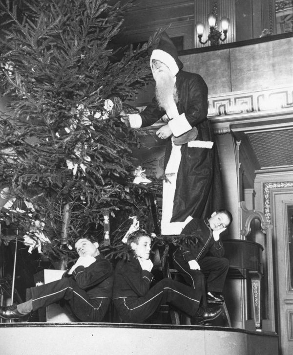 Father Christmas with page boys around a Christmas tree in 1934.