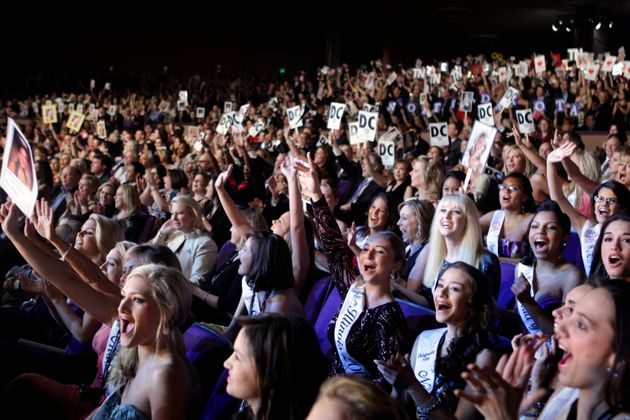 Audience members cheer contestants during the 2010 Miss America