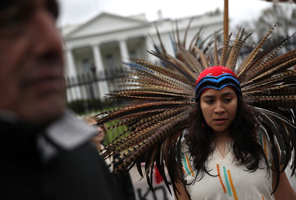 A Native American woman stands in front of the White House during a demonstration against the Dakota Access Pipeline on March