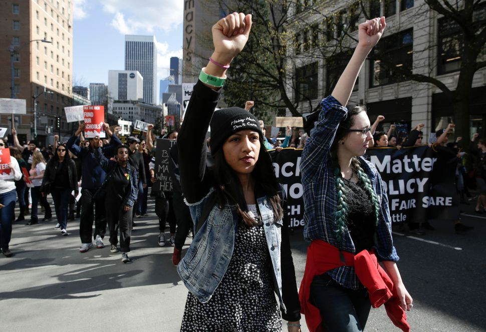 Women raise their fists and march at a Black Lives Matter protest in Seattle on April 15, 2017.