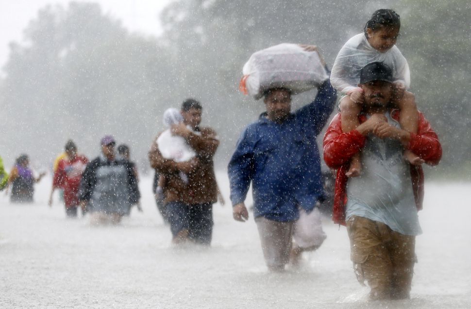 Residents wade through flood waters from Tropical Storm Harvey in Houston, Texas, on Aug. 28, 2017.