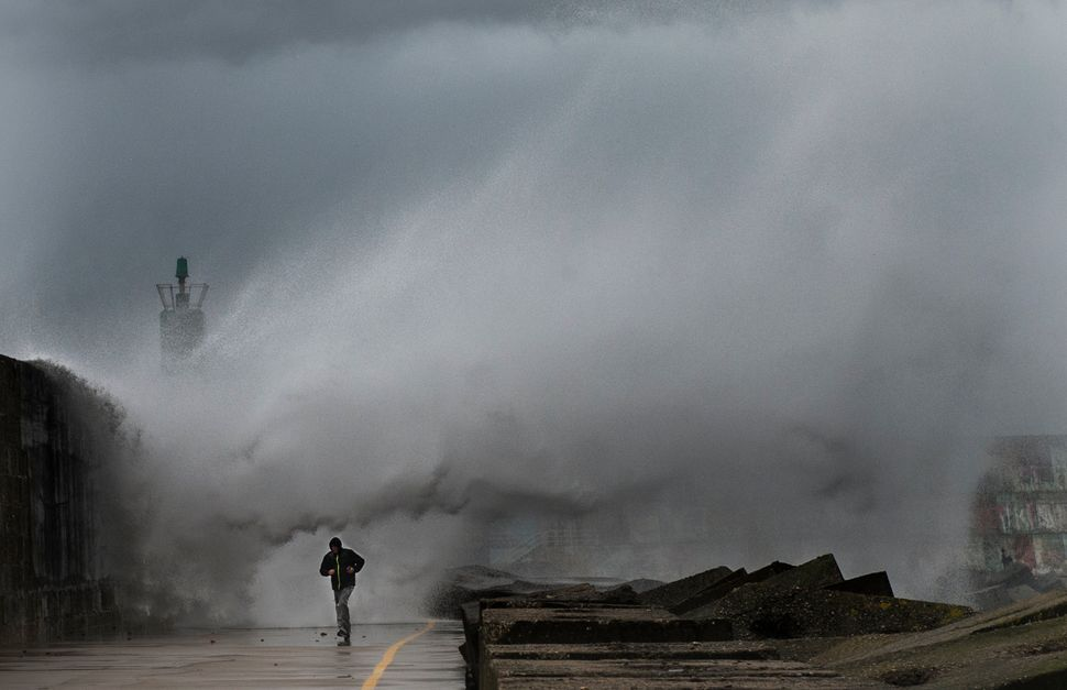 A man runs as a big wave hits the pier of the port of A Guarda in northwestern Spain during a storm on Feb. 2, 2017