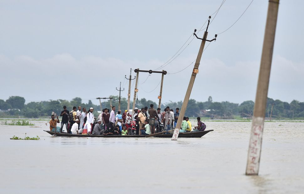 Indian villagers travel by boat through floodwaters on July 4, 2017.