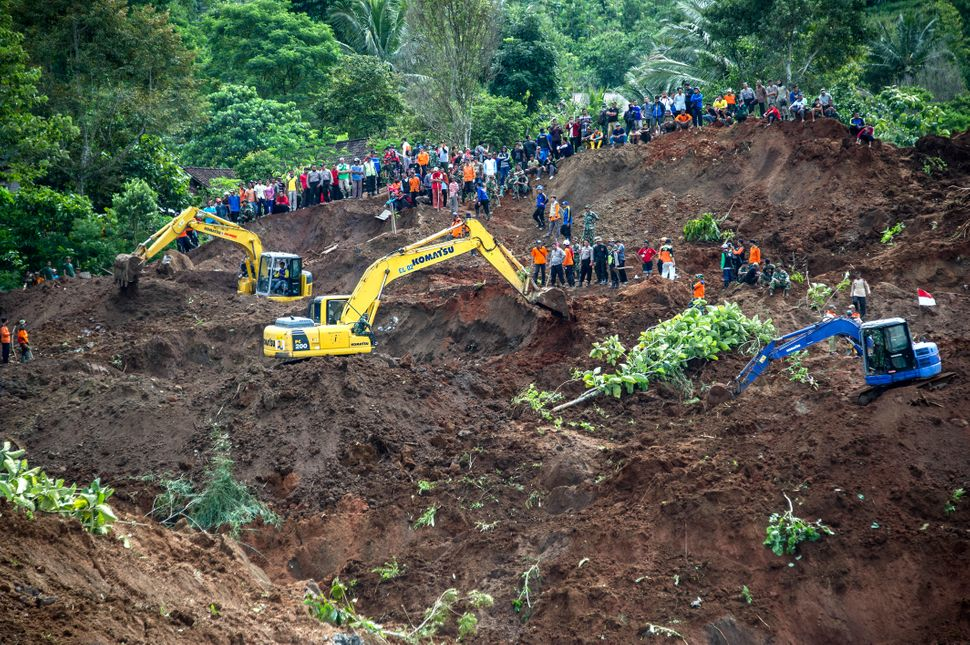 Indonesian rescuers search for survivors after a wall of mud slammed onto houses on a hillside after heavy rainfall on A