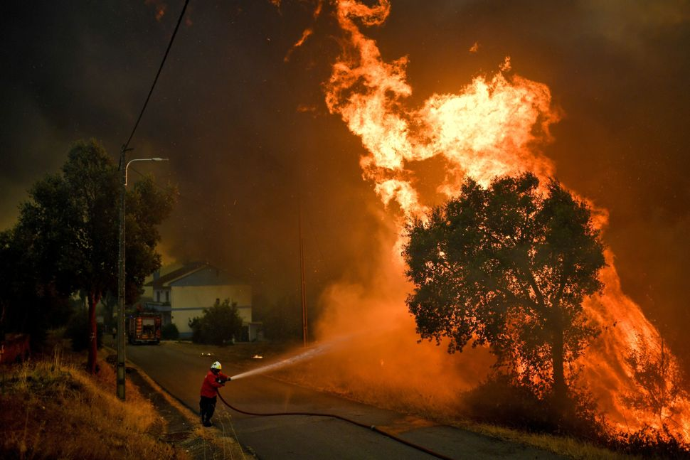 A firefighter tackles a wildfire close to the village of Pucarica in Portugal on Aug. 10, 2017.