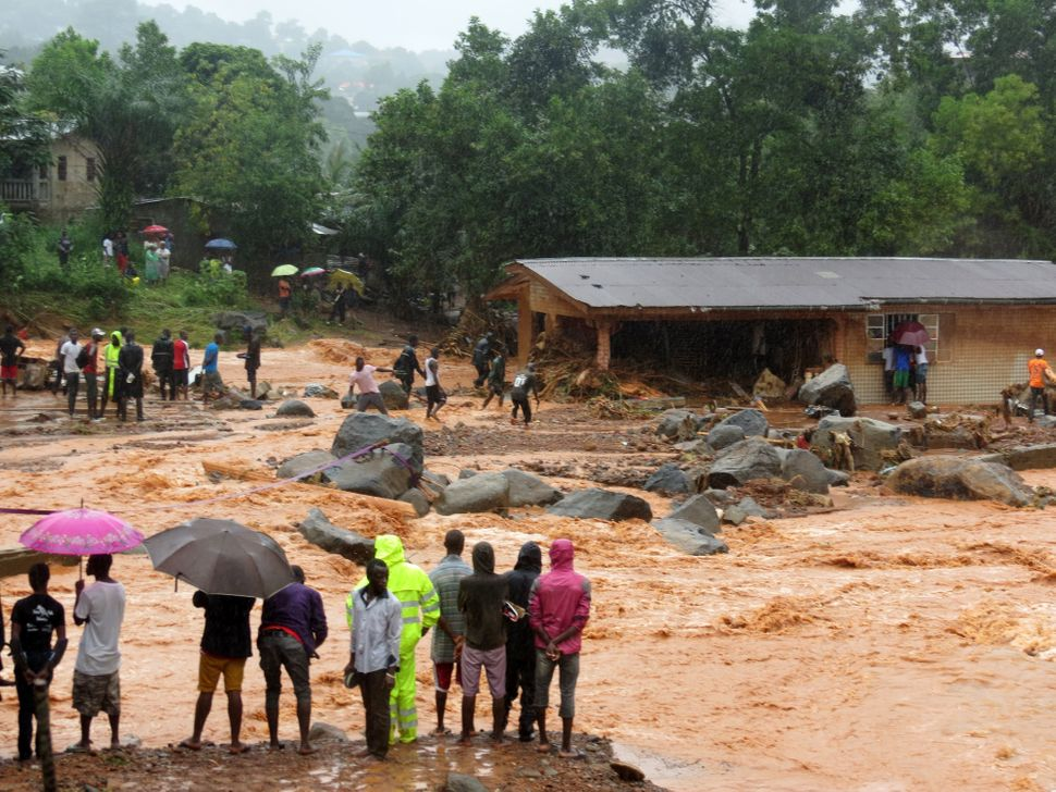 Bystanders look on as floodwaters rage past a damaged building in an area of Freetown onAug. 14, 2017, after landslides
