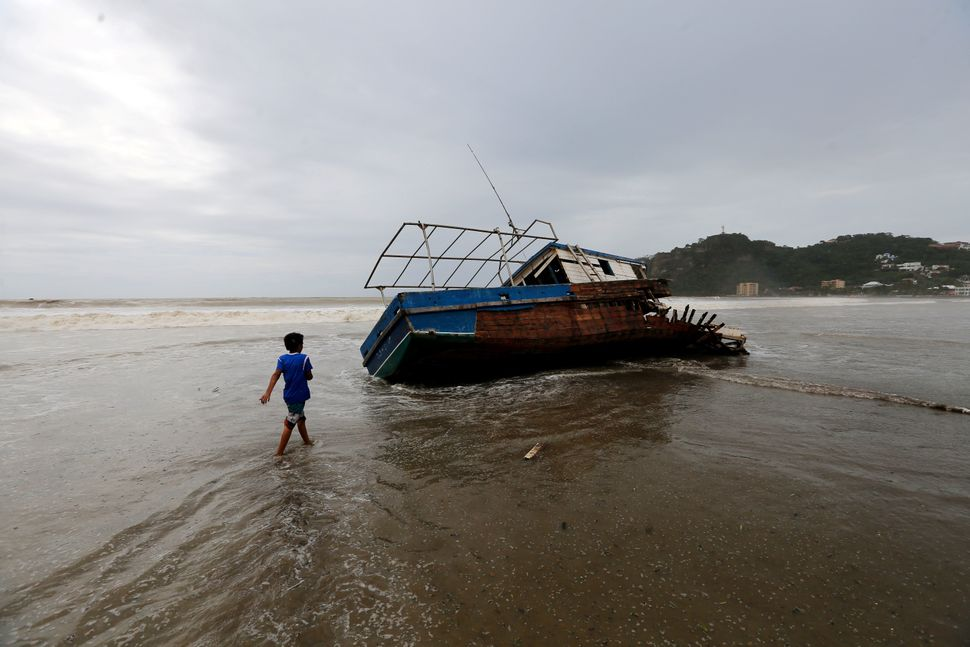 A boy walks towards a stranded boat in San Juan del Sur beach following the passage of Tropical Storm Nate in Nicaragua