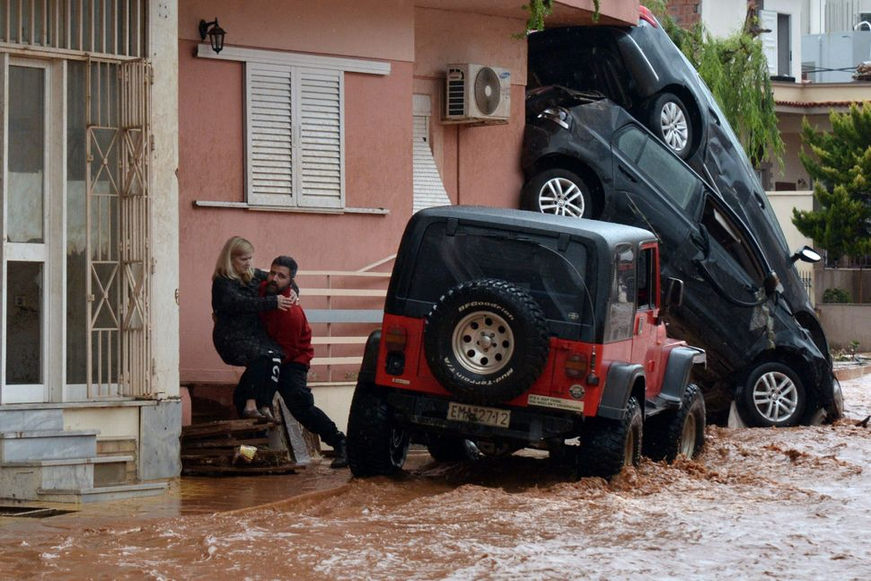 A man helps evacuate a woman from a flooded street in Mandra, northwest of Athens, Greece, on Nov. 16, 2017.
