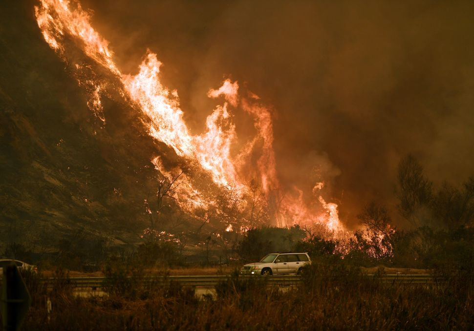 Vehicles pass beside a wall of flames on the 101 highway during a wildfire near Ventura, California, on Dec. 6, 201