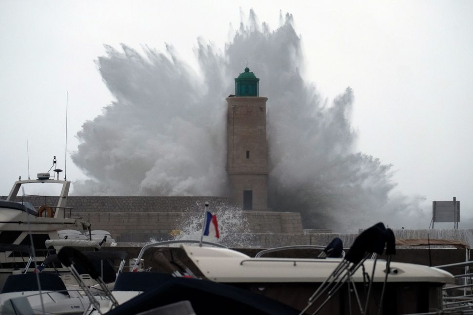 A wave breaks against a pier and a lighthouse as storm Ana smashes into Cassis, France, on Dec. 11, 2017.
