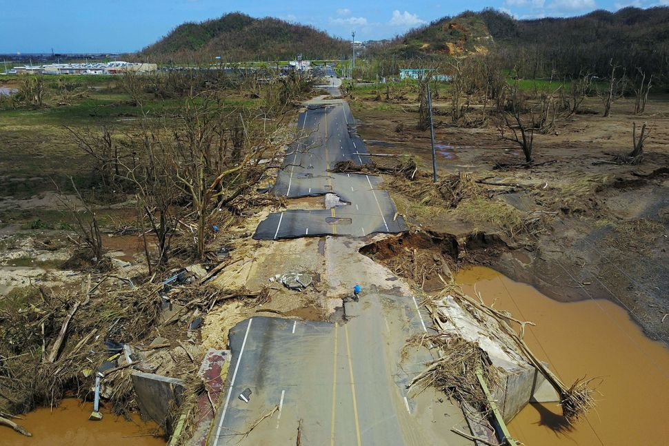A man rides his bicycle through a damaged road in Toa Alta, west of San Juan, Puerto Rico, onSept. 24, 2017, following