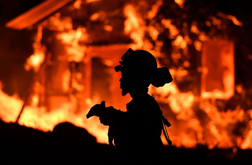 A firefighter monitors flames as a house burns in the Napa wine region in California onOct. 9, 2017.