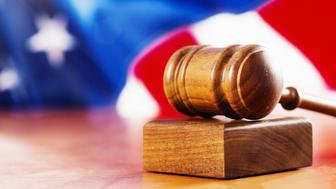 The American justice system, symbolized by a judge's gavel in front of a defocused American national flag.