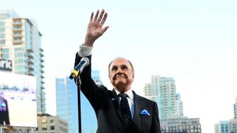 SAN DIEGO, CALIFORNIA - SEPTEMBER 29:  San Diego Padres announcer Dick Enberg waves to the crowd during a ceremony held before a baseball game between the San Diego Padres and the Los Angeles Dodgers at PETCO Park on September 29, 2016 in San Diego, California. The Padres held the pre-game ceremony to honor Enberg's last home game as the team's primary play-by-play man for television broadcasts.  (Photo by Denis Poroy/Getty Images)