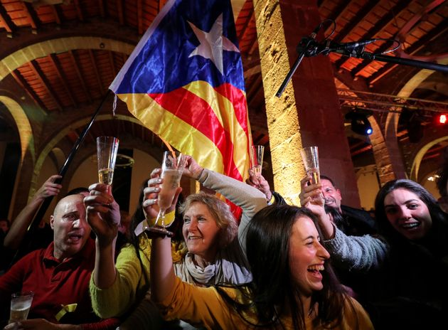 People react as results come in at a gathering of the Catalan National Assembly in