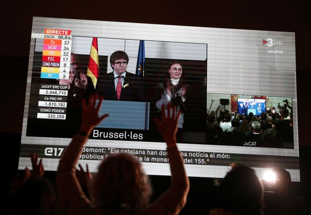 People watch Puigdemont speak on a giant screen in
