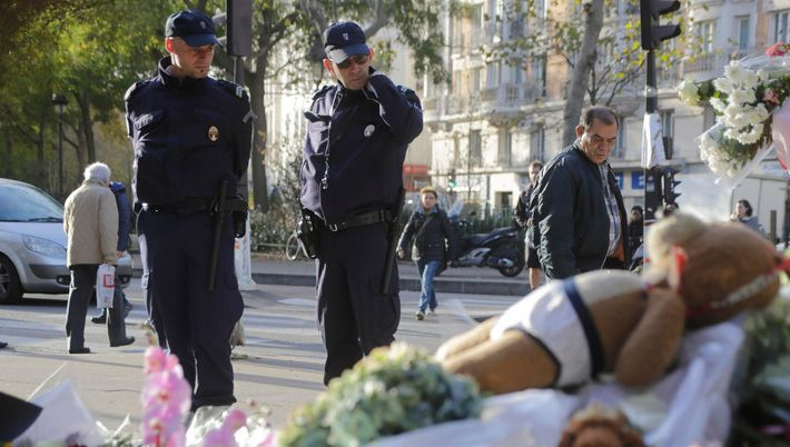 Policemen read messages which left at a makeshift memorial next to the  Bataclan concert hall in Paris, France, Wednesday, No