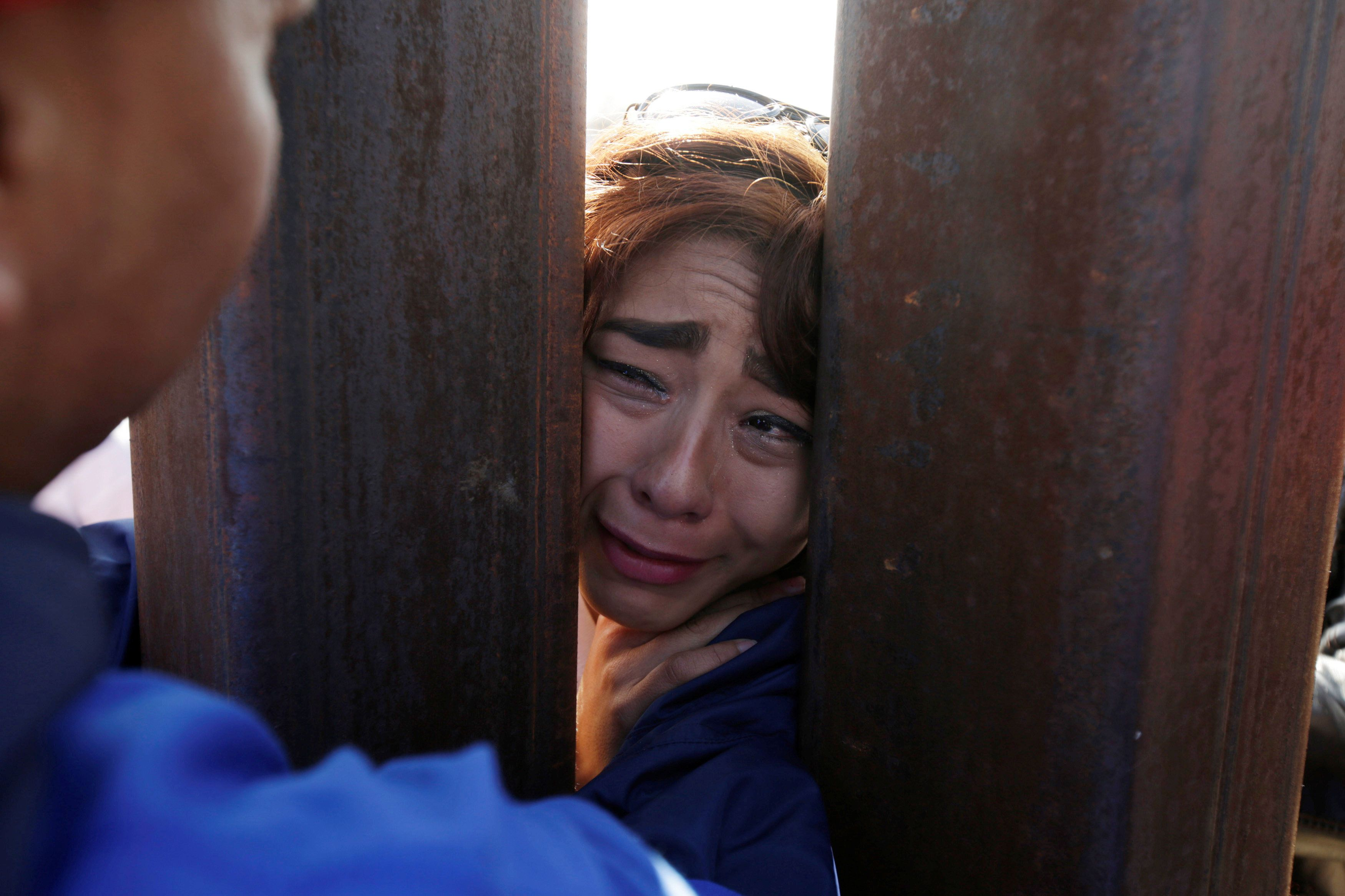 A woman cries as 'Dreamers' meet with relatives during the 'Keep Our Dream Alive' binational meeting at a new section of the border wall on the U.S.-Mexico border in Sunland Park, U.S., opposite the Mexican city of Ciudad Juarez, Mexico, December 10, 2017. Picture taken from the U.S side of the U.S.-Mexico border. REUTERS/Jose Luis Gonzalez