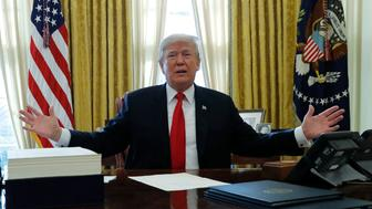U.S. President Donald Trump pauses next to the $1.5 trillion tax overhaul plan (L) while signing the bill in the Oval Office of the White House in Washington, U.S., December 22, 2017. REUTERS/Jonathan Ernst