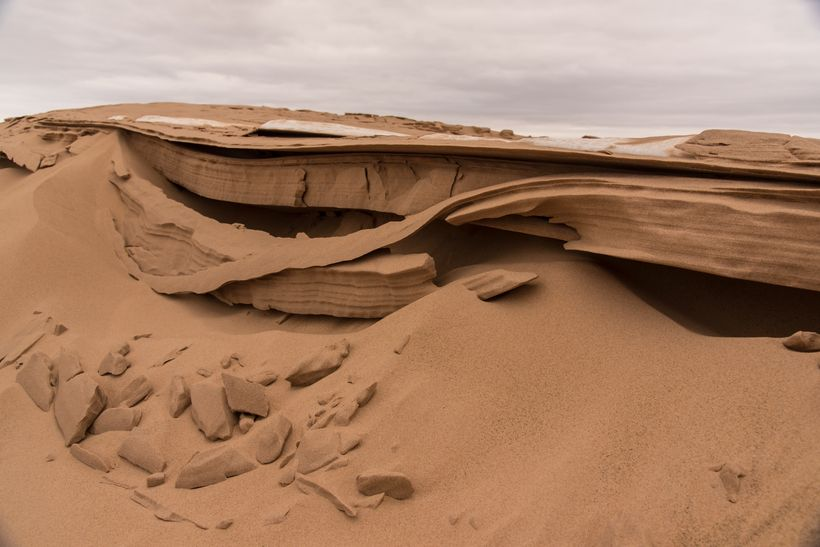 The wafer thin layers of sand, bending under the stress of gravity.