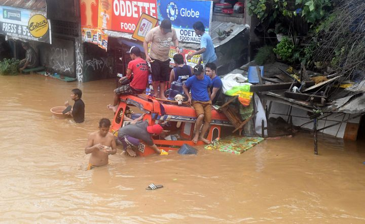 Residents are seen on the top of a partially submerged vehicle along a flooded road in Cagayan de Oro city in the Philippines