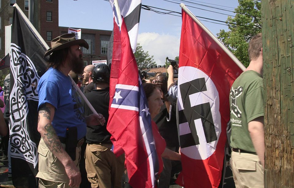 Marchers carry Confederate and Nazi flags during the Unite the Right rally in Charlottesville, Virginia,...